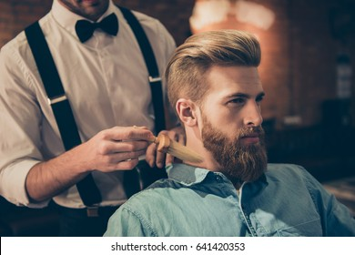 Classy dressed barber shop hairdresser is cleaning client`s neck with a brush and presents his work for him. Stunning! Hairdo looks trendy and so perfect