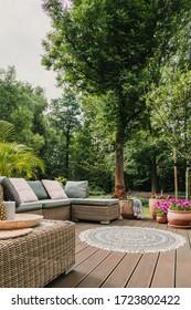 Classy furniture on wooden terrace in green beautiful garden