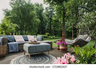 Kleine Möbel auf der Holzterrasse im schönen grünen Garten