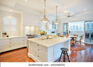 A classy kitchen and dining area featuring gas hob, dining set, cabinets, and hanging lights
