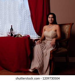 A classy latin woman waits at a table for her dinner date.