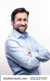 Classy look. The portrait of a handsome bearded middle-aged man in a baby blue shirt folding his arms across his chest and smiling at the camera