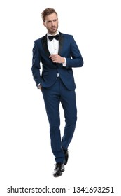 classy man in blue suit walking with hand in his pocket while looking away on white background