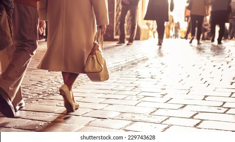 Classy older European woman walking on stone tiled path holding a handbag.