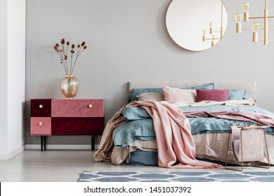 Classy round mirror on grey wall in stylish bedroom interior with warm bed with blue, pastel pink and beige bedding and velvet covered nightstand