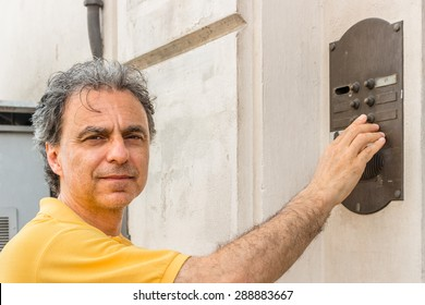 Classy senior sportsman with three-day beard and salt and pepper hair wearing a yellow polo shirt while he is ringing a doorbell of an apartment building in residential neighborhood