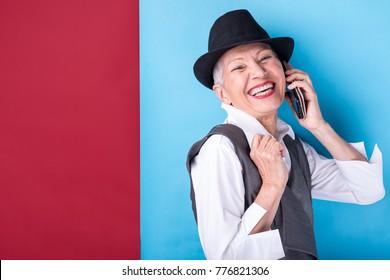 Classy senior woman having a joyful conversation over her cell phone