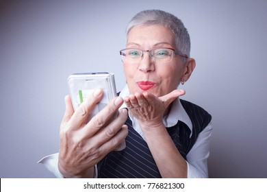 Classy senior woman sending kisses over social media to her family and relatives