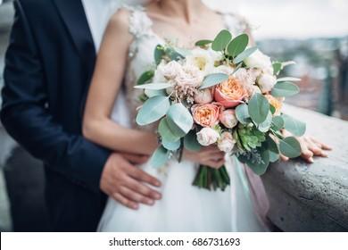 ゴシック様式の大聖堂の屋根に抱き合う高級な結婚式のカップル