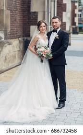 Classy wedding couple poses on the old European street