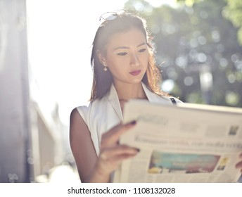 Classy woman reading a newspaper