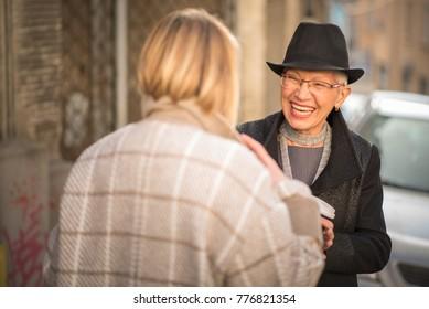 Classy women, two friends, talking, making jokes and having fun, urban outdoor area