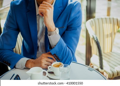 Classy young european businessman in a blue suit in Parisian outdoors cafe