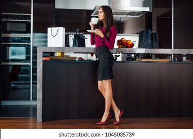 Classy young Latin woman drinking coffee standing in the kitchen relaxing after shopping