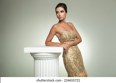 classy young woman in long elegant dress, standing near column and looks away in studio