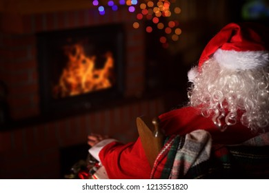 Claus is sitting in front of the fireplace