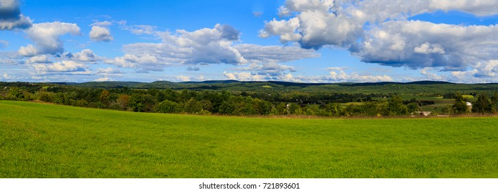 Claverack NY area in the Hudson Valley looking at trees, rolling hills, green meadows and farmland in later afternoon in summer.