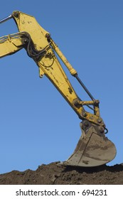 The claw of a backhoe works on a pile of dirt.