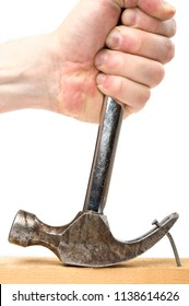 Claw hammer pulling a nail out of a plank.