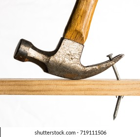 A claw hammer is shown removing a large galvanized nail from a piece of wood