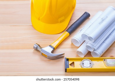 claw hammer  stack of white rolled blueprints construction level helmet on wooden boards