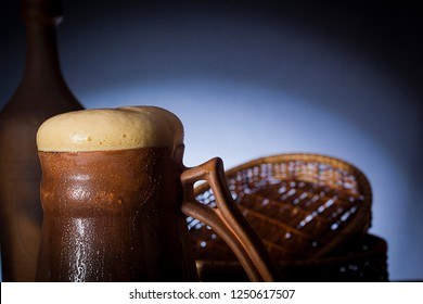 Clay beer glass with beer and bottle