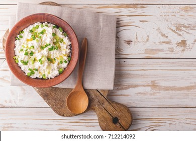 Clay bowl of goat cream cheese with green onions and olive oil, dip sauce on wooden table, top view