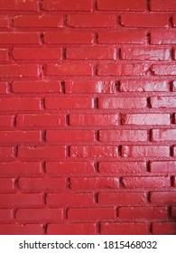 Clay brick walls painted with red oil paint have a sheen and reflect light at some point.