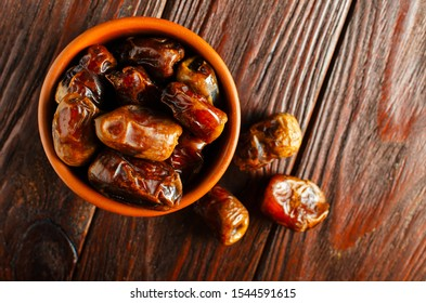 Clay brown bowl with dried dates on a wooden table. Healthy sweets, healthy nutrition. Traditional dessert in ramadan. Flat ley