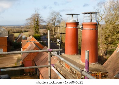 Clay chimney pot with cowl on a roof, repairing chimney with scaffolding UK