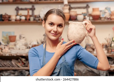Clay craft. Young and smiling female potter holding a jar on her shoulder