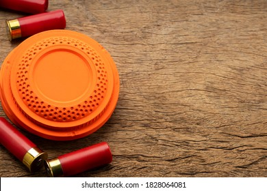 Clay disc flying targets and shotgun bullets on wooden background ,Clay Pigeon target