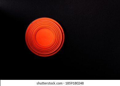 Clay disc target for skeet shooting against the black background. Half lit effect. Copy space