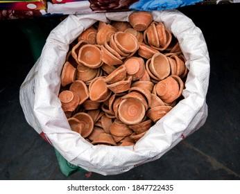 clay diwali diya light lamps in white bag near little stall for sale, for diwali festival.