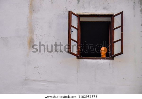 Clay face of beautiful woman and structure wall of old house with wooden window make unique atmosphere.