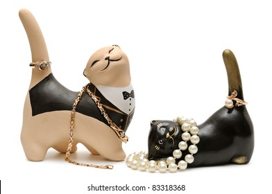 Clay figurines of cats with golden ornaments. Isolated on white background.