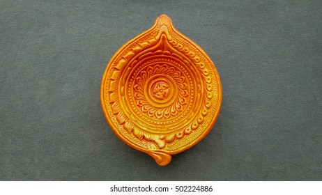 Clay golden colored oil lamp for Indian Diwali festival isolated on gray cotton background