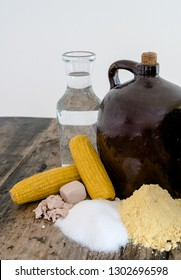 A clay half gallon jug with cob stopper and the ingredients for making moonshine corn liquor on a rustic wooden table