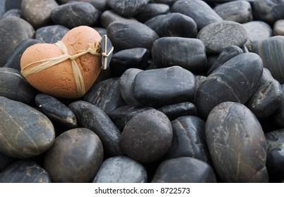 A clay heart on black gravel