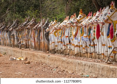 Clay horses assembled in homage to the Hindu god Ayyanar outside a temple in Tamil Nadu, India. Ayyanar is the mythical guardian of local villages which he reputedly patrols at night on horseback