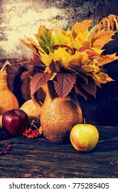 Clay jug with autumn leaves next to harvest of apples and pumpkins on wooden desk. Mockup for seasonal offers and holiday post card