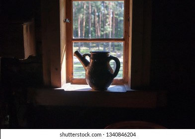 Clay jug stands on the window. Old wooden country house.