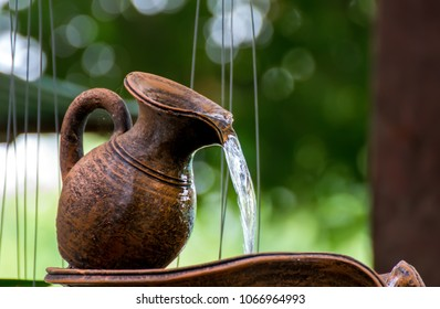 clay jug,water is drop from clay jug in the garden.