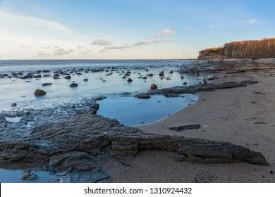 Clay layer sticks out of the calm sea water.