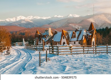 Clay (loam) Castle in winter with sunset, The Valley of the Fairies (Castelul de Lut, Valea Zanelor), Transylvanian Hobbit hotel built out of clay and sand in Romania, Porumbacu de Sus. Grimm houses.