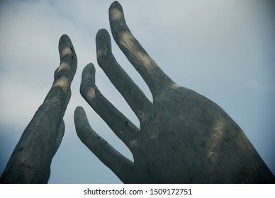 Clay made fingers of human hands with sky background photo