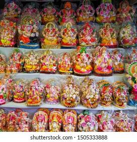 clay made hindu god ganesha colorful statue at market shop, west bengal, india.