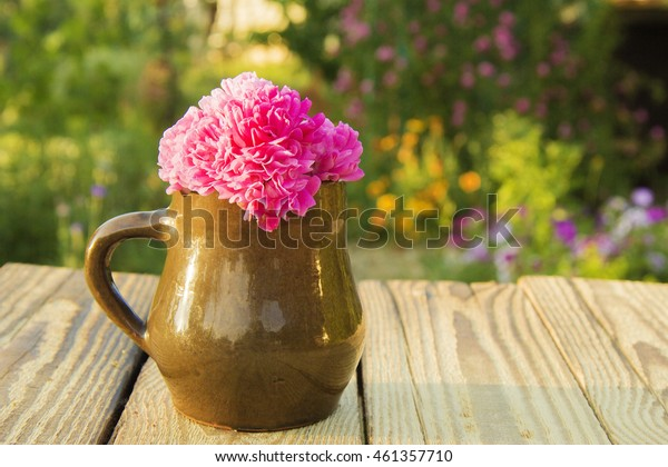 clay mug with flower pink roses on a wooden table