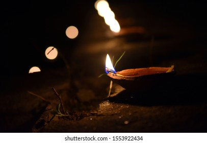 Clay oil lamp (Diya) Burning in the Dark night with blurred clay oil lamp lights background
