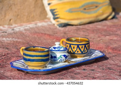 Clay ornamental cups of tea on a carpet at traditional Persian chaikhana (tea cafe) in Iran